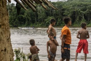 Children watch a boat go past on the river in the Waikas community