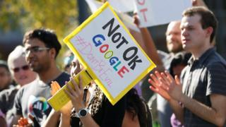 "A Google employee (centre) holds a sign that reads ""Not OK Google"" during a walkout in Mountain View, California"