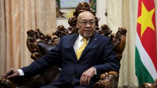 President Desi Bouterse sitting in a wooden chair with a red flag beside him