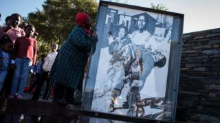 A woman holds the iconic photograph taken by legendary photographer Sam Nzima in 1976