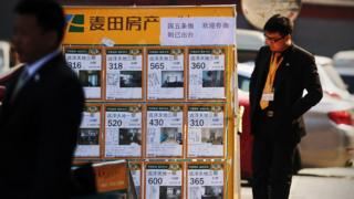 A man looking at a property advertising board in Beijing