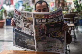 "A man reads a newspaper with a headline concerning diplomatic tensions between Turkey and The Netherlands, which translates as ""What a Barbarism"" in Istanbul on 13 March, 2017"