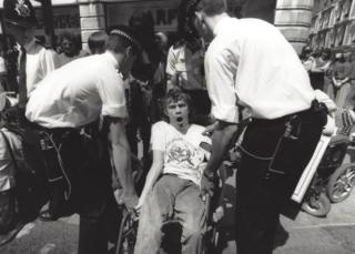 A wheelchair user being lifted up by police
