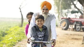 Idoso com duas crianças sorrindo na bicicleta