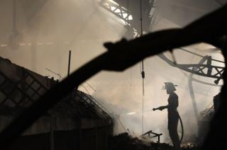 Fire fighters work to put out a blaze at Port-au-Prince's historic Iron Market.
