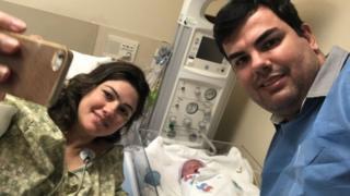 Thiago Panes e Miriane Becker tirando foto com filho recém-nascido
