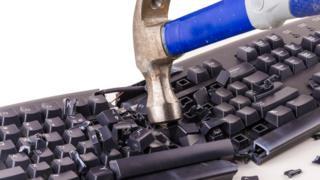 Un teclado recibiendo un martillazo