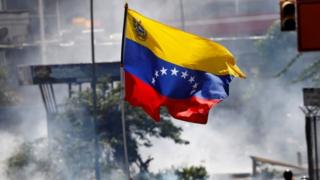 """a Venezuelan flag during riots at a march to state Ombudsman""""s office in Caracas, Venezuela May 29, 2017."""