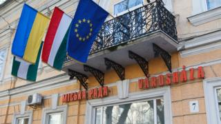 From left to right: Ukrainian, Hungarian and EU flags and inscriptions in Ukrainian and Hungarian on a city hall building of Berehove, western Ukraine. File photo