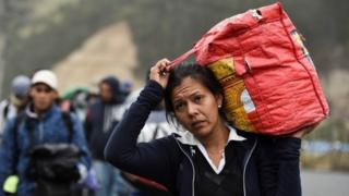 A Venezuelan woman who has emigrated carries a bag along the Pan-American highway
