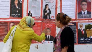 امرأتان أمام ملصقات دعائية للمرشحين