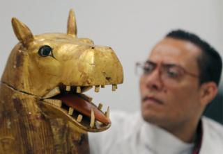 A golden sculpture of an animal is seen inside a workshop. Behind it, a specialist looks on.