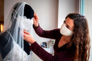 A woman adjusts the face mask on a mannequin that is wearing a wedding dress