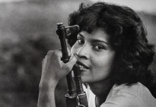 A picture of a medical student with a rifle in the 1980s
