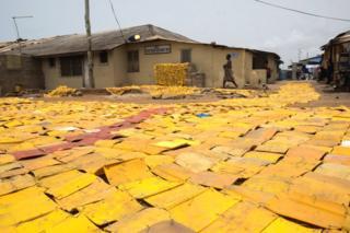 Yellow tapestry created by artist Serge Attukwei Clottey on a road in La - Accra, Ghana