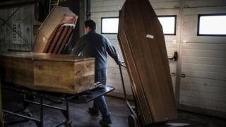 A coffin-maker with three coffins
