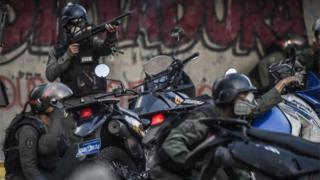 Venezuelan security forces take cover upon coming under fire during a confuse skirmish in Caracas on July 30, 2017