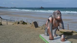 Gorilla in front of beach and tower