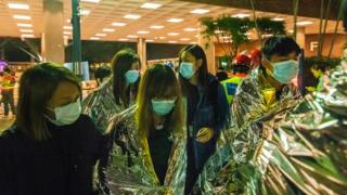 Injured protesters wrapped in emergency thermal blankets leave the campus of the Hong Kong Polytechnic University