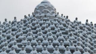 Buddha statues are covered with snow at a temple