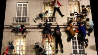 People experience the Building installation during the exhibition by Argentine artist Leandro Erlich.