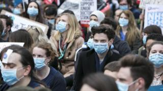 "Junior doctors and their supporters stage a ""masked march"" protest in London on February 6"
