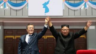Moon Jae-in and Kim Jong-un raise held hands aloft
