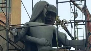 The Mother of the Martyr sculpture, which depicts a slender peasant woman, a traditional artistic representation of Egypt, with her arms outstretched with a helmeted soldier standing behind her, at a public square in Sohag, Egypt