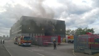 Smoke emanating from an industrial waste site building