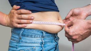 врач измеряет талию полного человека