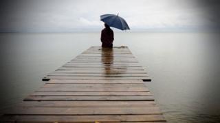 Женщина под зонтиком на берегу