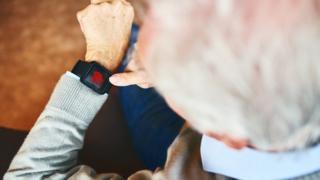 Homem com cabelos brancos olha para relógio de pulso, que exibe um coração