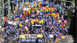 """Avusturalya'da balonlarla yürüyen kalabalık pankartlarına """"Biz kazanıyoruz"""" yazdı."""