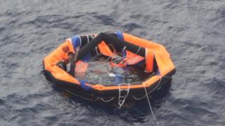 A Filipino crew member of the Gulf Livestock 1 waves from a life raft in the East China Sea on 04 September 2020