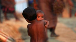 A Rohingya Muslim child carries an infant at a refugee camp in Palang Khali near Cox's Bazar, Bangladesh.