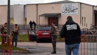 French police officers and soldiers stand near a red car in front of the mosque of Valence, southeastern France, on January 1, 2016,