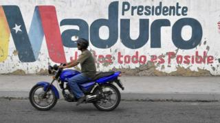 A motorcyclist rides in front of a mural with the surname of Venezuelan President Nicolas Maduro in Caracas, Venezuela