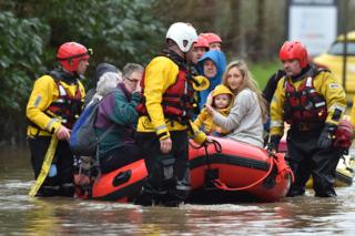 Residents of Nantgarw in a rescue boat as emergency services take people to safety, after flooding in the village in Wales