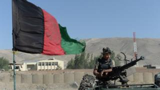 An Afghan security force member keeps watch at the site of a suicide attack in Maidan Shar, the capital city of Wardak province south of Kabul
