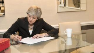 Theresa May sitting at desk singing papers