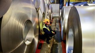 worker inspects rolls of steel