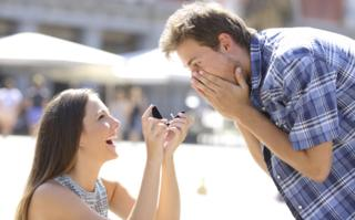 Stock image of a woman proposing to a man