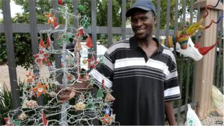 A vendor sells a hand made Christmas tree in Johannesburg, file