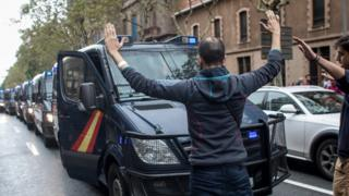A man blocks a line of police truck as they try to control the area as people wait to cast their ballot in the referendum vote at Escola Industrial of Barcelona school polling station on October 1, 2017 in Barcelona, Spain.