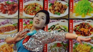 Официантка танцует на фоне меню северокорейского ресторана в Китае