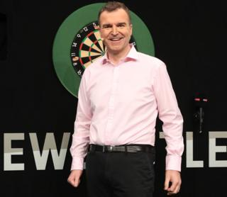 Dave Clark in front of a dart board in Newcastle