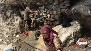 люди набирают воду у родника