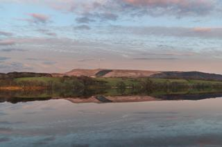 Hills reflected in water