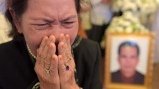 A Cambodian woman cries near a portrait of Kem Ley (R), a political analyst and pro-democracy campaigner, during a funeral ceremony in Phnom Penh on July 12, 2016