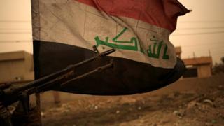 Iraqi flag seen during a sand storm in Bartella, east of Mosul, Iraq (1 November 2016)